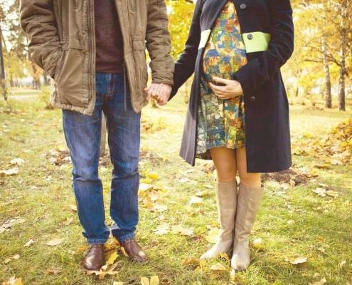 Eine schwangere Frau mit Partner in der Natur
